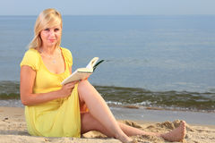 Robe de jaune de fille de livre de lecture de femme Image stock
