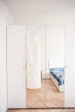 Robe de mariage accrochant sur le lustre à la chambre d'hôtel Photo stock