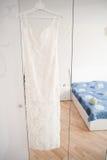 Robe de mariage accrochant sur le lustre à la chambre d'hôtel Photographie stock