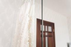 Robe de mariage accrochant sur le lustre à la chambre d'hôtel Images libres de droits