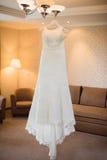 Robe de mariage accrochant sur le lustre à la pièce Image stock