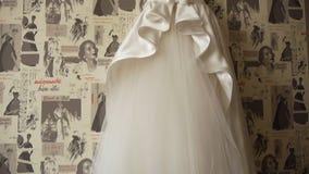 Robe de mariage accrochant sur un cintre au mur, une jeune mariée se préparant au mariage clips vidéos