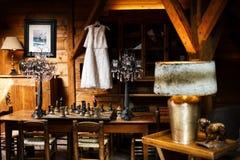 Robe de mariage accrochant sur un cintre dans une salle, un placard, des tables, de grands échecs et des lampes Photo stock