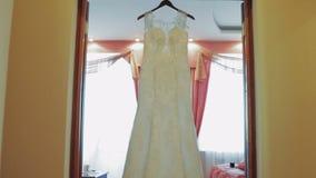 Robe de mariage blanche accrochant à la porte banque de vidéos