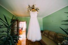 Robe de mariage blanche d'Ellegant accrochant sur le lustre à la chambre d'hôtel décorée des usines exotiques Image libre de droits