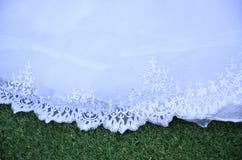Robe de mariage blanche de dentelle d'ourlet sur l'herbe verte Image stock