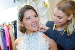 Robe de mariage de essai femelle dans la boutique avec des femmes auxiliaires photo stock