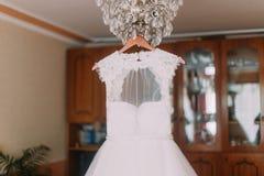 Robe de mariage luxueuse accrochant sur le lustre au vestiaire Images libres de droits