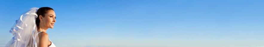 Robe de mariage de port de Web de jeune mariée panoramique de bannière avec le ciel bleu image stock