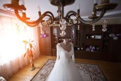 robe de mariage se tenant dans une jeune mariée luxueuse de pièce Photo stock