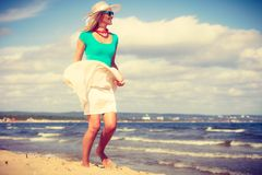 Robe de port de femme blonde marchant sur la plage Photo stock