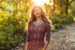 Robe de port de jeune femme, dans le contre-jour de forêt par la lumière de coucher du soleil Photos libres de droits