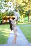 Robe de port de jeune femme européenne tenant peu de bébé dans le jardin photo stock