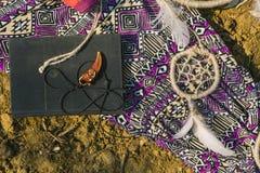 Robe, dreamcatcher et livre se trouvant sur la terre sèche Style de hippie Image libre de droits