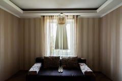 Robe du ` s de jeune mariée accrochant sur le support près de la fenêtre dans la chambre image stock