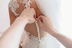 Robe du ` s de jeune mariée se boutonnant Vue de la première personne Image stock