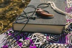 Robe et livre se trouvant sur la terre sèche Style de hippie Images stock