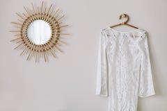 Robe l'?pousant blanche accrochant dans la chambre ? coucher La garde-robe de la fille Robe de dentelle à côté du miroir photos stock