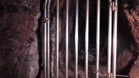 Robe la jaula en la entrada de la montaña a la mina, Moria, cárcel, prisión almacen de video