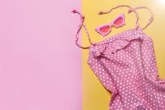 Robe plate d'ofPink de configuration et lunettes de soleil roses sur le fond rose et jaune Vue supérieure, configuration plate Vê Image stock