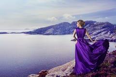 Robe pourpre de femme, regardant la mer de montagnes, fille élégante sur la côte Photographie stock libre de droits