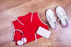 Robe rouge, espadrilles, écouteurs, portefeuille Photo stock