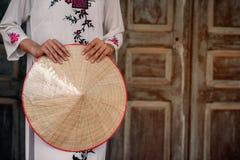 Robe traditionnelle du Vietnam avec tenir le chapeau Photos stock