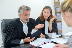 Robed lawyer in meeting with client. Magistrate stock images