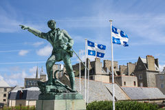 Robert Surcouf and quebec flags. View of a statue of Robert Surcouf in front of two quebec flags in Saint-malo in France royalty free stock images