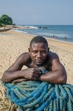 Robertsport, Liberia - January 26, 2014: Portrait of African fisherman leaning on nets at beach Royalty Free Stock Image