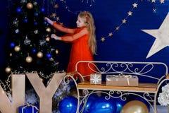 Robes de fille un arbre de Noël avec des guirlandes et des jouets photo stock