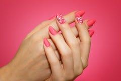 Robiący manikiur kobiety ` s gwoździe z różowym nailart z kwiatami Obraz Royalty Free