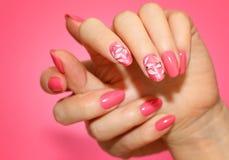 Robiący manikiur kobiety ` s gwoździe z różowym nailart z kwiatami Zdjęcia Royalty Free