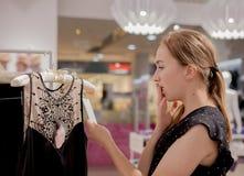Robiący zakupy, moda, ubrania, projektuje pojęcie i zaludnia Szczęśliwa młoda kobieta patrzeje metki etykietkę w centrum handlowe Obrazy Royalty Free