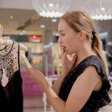 Robiący zakupy, moda, ubrania, projektuje pojęcie i zaludnia Szczęśliwa młoda kobieta patrzeje metki etykietkę w centrum handlowe Zdjęcie Royalty Free