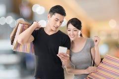 Robiący zakupy telefon komórkowego i patrzejący zdjęcie stock