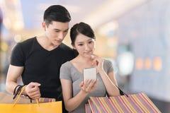 Robiący zakupy telefon komórkowego i patrzejący fotografia stock