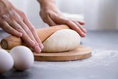 Robić ciastu kobiet rękami na drewnianym stołowym tle Obrazy Stock
