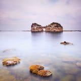 Robić dziurę wyspę i skały w tropikalnym błękitnym oceanie. Chmurny niebo. Zdjęcie Stock