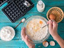 Robić gofrom mleko, jajka i mąka w domu, - gofra żelazo, ciasto naleśnikowe w pucharze i składniki, - zdjęcie stock