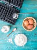 Robić gofrom mleko, jajka i mąka w domu, - gofra żelazo, ciasto naleśnikowe w pucharze i składniki, - fotografia stock