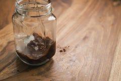 Robić kakaowemu napojowi w szklanym słoju z rękojeścią na drewno stole, dodaje wodę Zdjęcie Royalty Free