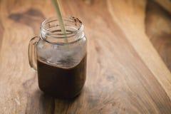 Robić kakaowemu napojowi w szklanym słoju z rękojeścią na drewno stole, mleko nalewa Obraz Stock