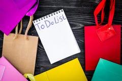 Robić liście dla robić zakupy wśród kolorowych papierowych toreb na popielatego drewnianego tła odgórnym widoku Zdjęcie Royalty Free