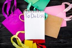 Robić liście dla robić zakupy wśród kolorowych papierowych toreb na popielatego drewnianego tła odgórnym widoku Obrazy Stock