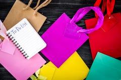 Robić liście dla robić zakupy wśród kolorowych papierowych toreb na popielatego drewnianego tła odgórnym widoku Obrazy Royalty Free