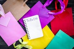 Robić liście dla robić zakupy wśród kolorowych papierowych toreb na popielatego drewnianego tła odgórnym widoku Zdjęcia Royalty Free