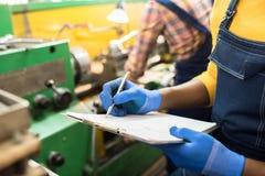 Robić notatkom o fabrycznej maszynie obrazy royalty free