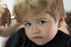 Robić ostrzyżeniu grze Chłopiec z blondynem przy fryzjerem Małe dziecko dawać ostrzyżenie Mały dziecko wewnątrz zdjęcia royalty free