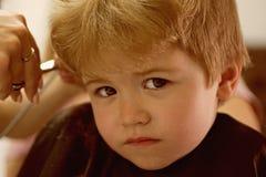 Robić ostrzyżeniu grze Chłopiec z blondynem przy fryzjerem Małe dziecko dawać ostrzyżenie Mały dziecko wewnątrz fotografia royalty free
